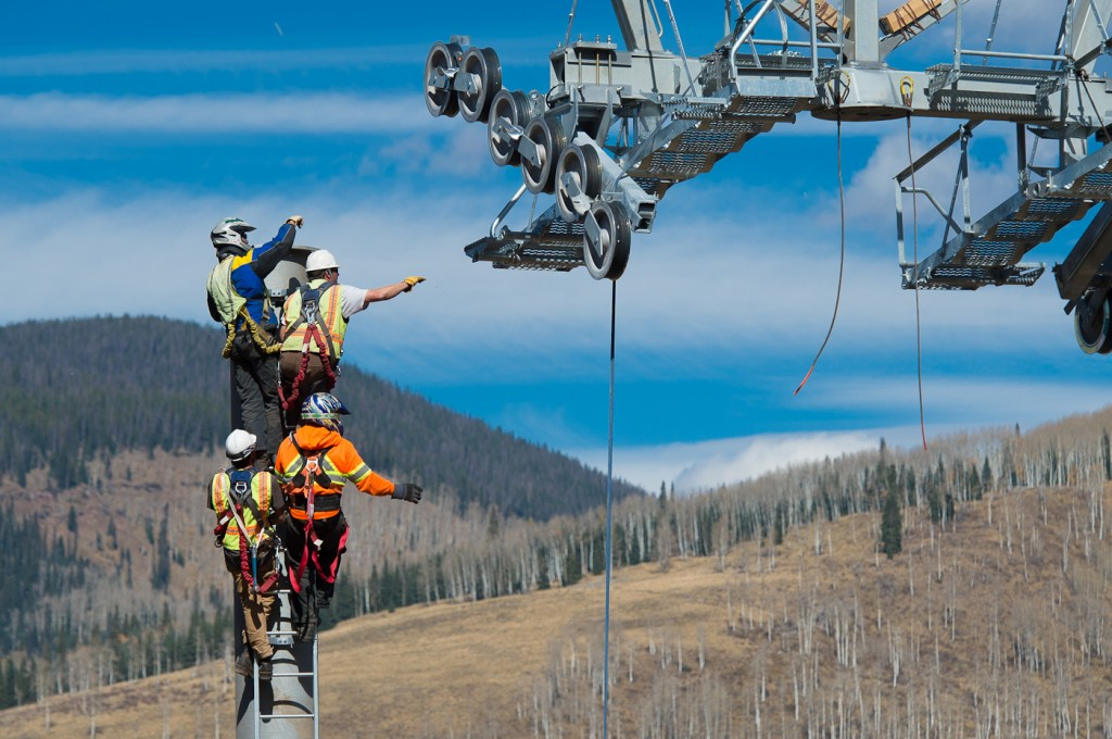Workers reach for guide wires on Vail gondola tower