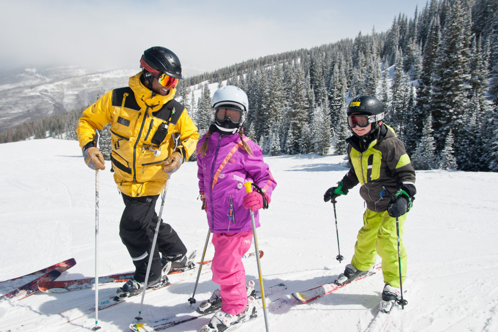 Mountain Safety staff talking to two kids on skis