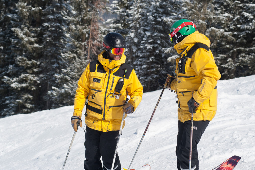 Two Vail Mountain Safety employees discuss skier and rider speed on Flapjack
