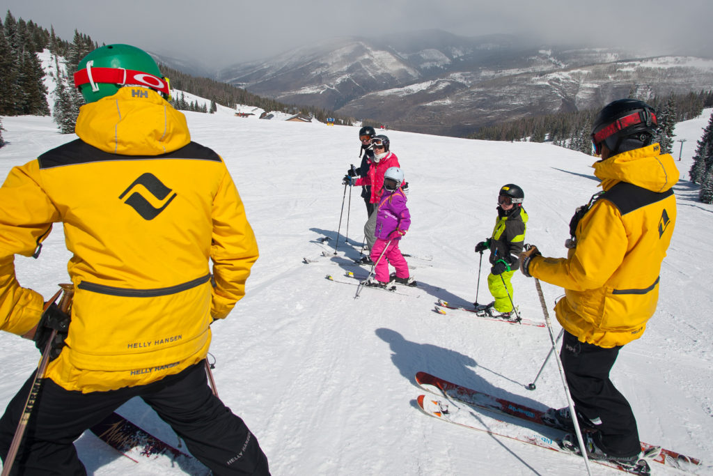 Two mountain safety talking to a family on skis